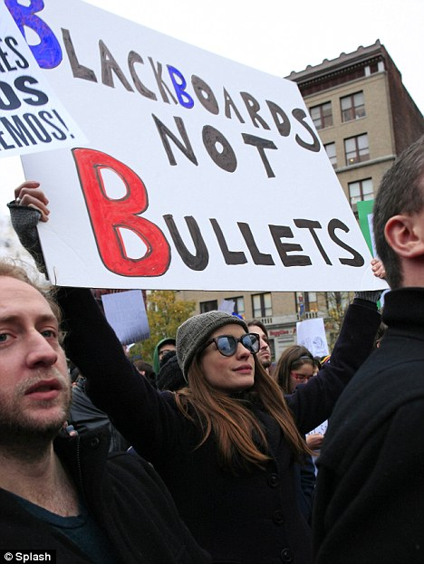 Star power: Anne Hathaway carries a sign reading 'Blackboards not Bullets' as she protests yesterday in New York
