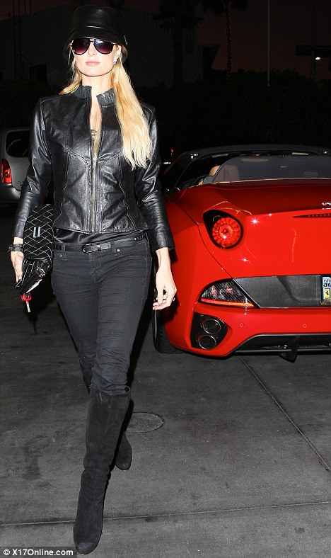 Showing off: Paris Hilton loved parading around in her new Ferrari when most people were hunting for bargains last night