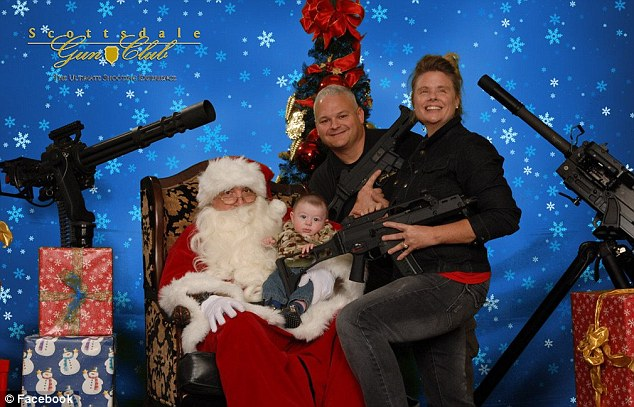 Starting young: A baby reaches for a gun in a photograph taken at the first Christmas photo event last year