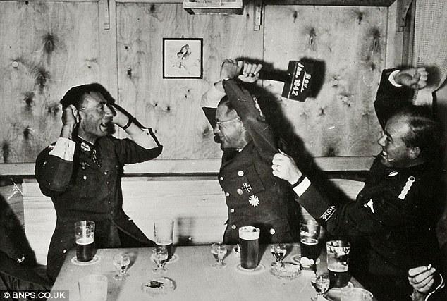 Two German officers partake in a drunken drinking game in a bar in Norway in July 1942 - one wields a mallet in an apparent joke