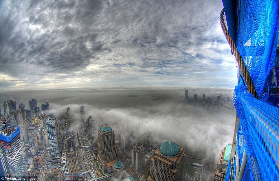 Towering symbol: The fog rolls out across downtown Manhattan, captured from the 80th floor of One World Trade Center