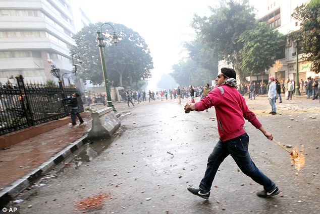 Retaliation: A protester throws a make-shift fire bomb near the Parliament building