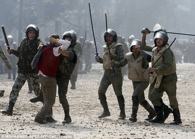 Brutal: Egyptian soldiers beat a protester after petrol bombs are thrown outside the Cabinet building in Cairo