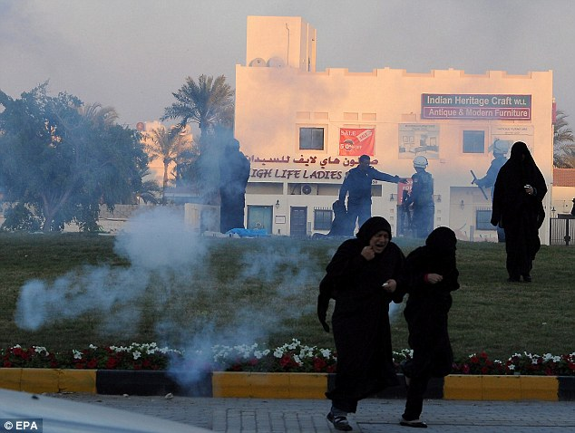 Under-fire: Pro-reform female protesters run for cover as heavy-handed police try to disperse them with tear-gas, in Abu Seba village, north of Manama, Bahrain