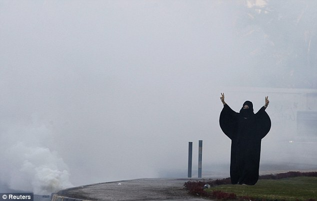 Defiant: A brave woman shouts anti-government slogans as she stands amidst tear gas fired by riot police to disperse a sit-in at a roundabout on Budaiya Highway, west of Manama