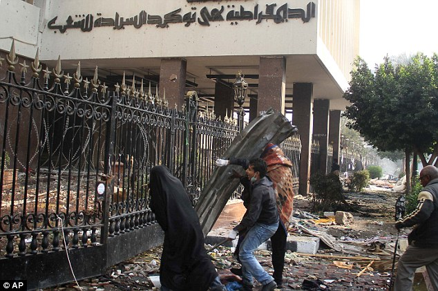 Protection: A female and two male Egyptian protester use a metal sheet as a shield as they throw rocks at military police, unseen, behind the gates and inside the Parliament building near Cairo's Tahrir Square