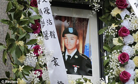 Sadness: A portrait of U.S. Army Private Danny Chen is displayed during his funeral procession in New York on October 13 after his death in Afghanistan