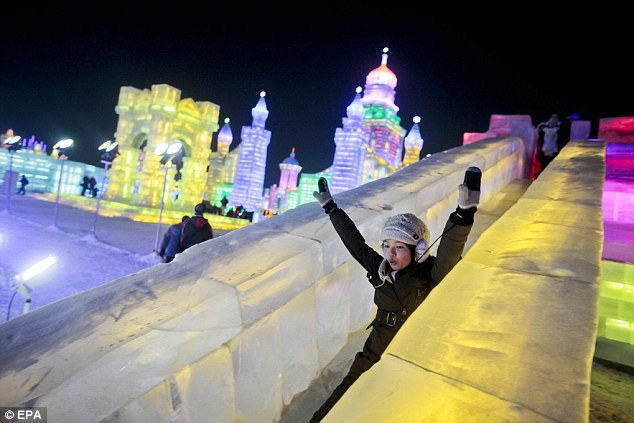 What goes up, must come down: A female ice-lover zips down one of the slides at the event