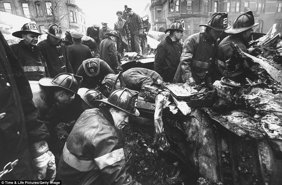 Grisly sight: Firemen, each wearing expressions of horror, pull corpses from the wreckage of the flight. There were 83 people aboard United Airlines Flight 826