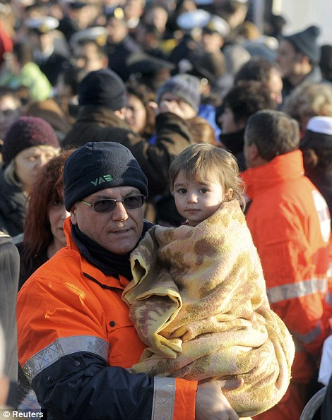 A rescue worker carries a child