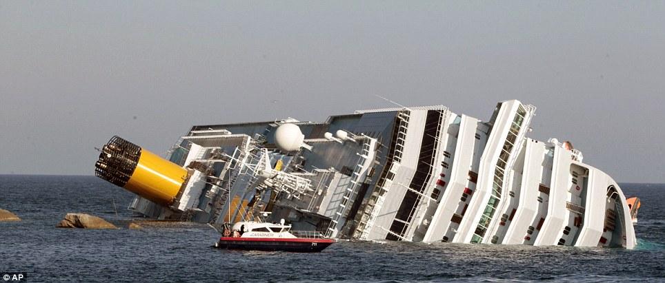 Un bateau Carabinieri approches du Costa Concordia comme elle repose partiellement immergé dans l'eau au large des côtes de la Toscane