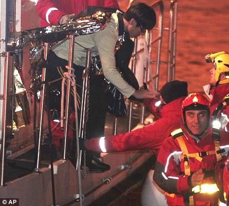 Chanceux d'être vivant: un passager de la Corée du Sud, au centre, est amené à la sécurité par les pompiers italiens après les secouristes l'ai trouvé dans le navire partiellement coulé