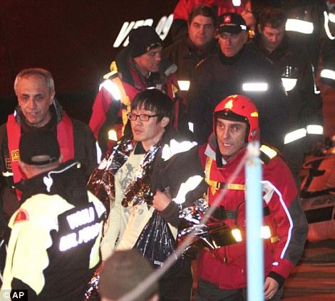 Un passager de la Corée du Sud, au centre, est amené à la sécurité par les pompiers italiens