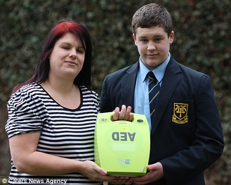 Caullum, pictured with his mother Lynne and a defibrillator, which gives the heart an electric shock in cases of cardiac arrest