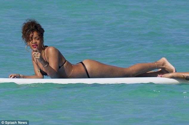 Not camera shy: Rihanna points knowingly at the onlooking paparazzi