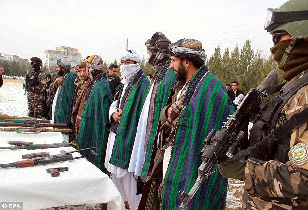 Surrender: A group of seven Taliban militants give up their weapons during a reconciliation ceremony in Herat, Afghanistan, earlier today