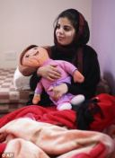 Baraa Melhem, 20, holds a doll, in her room at her mother's house in the West Bank village of Qalandia, near Ramallah