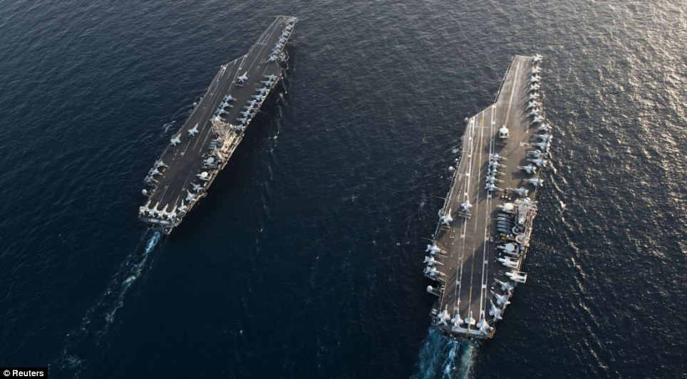 Under pressure: USS John C. Stennis (L) and USS Abraham Lincoln (R) pictured last week. Yesterday they passed through the strait. Today the EU are expected to impose an oil embargo