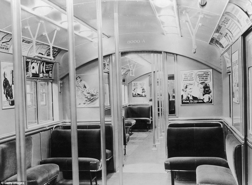 Travelling in style: An interior view of a subway car shows how passengers travelled in 1935. It shows upholstered seats, and advertising posters for cigarettes, cold medicine and dog food