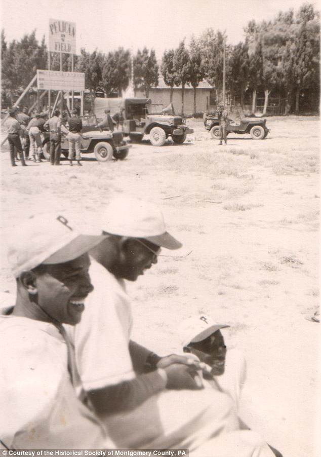 Work and play: This picture shows the men in the foreground relaxing while presumably taking time out to play baseball on an Army base given the Jeeps in the background
