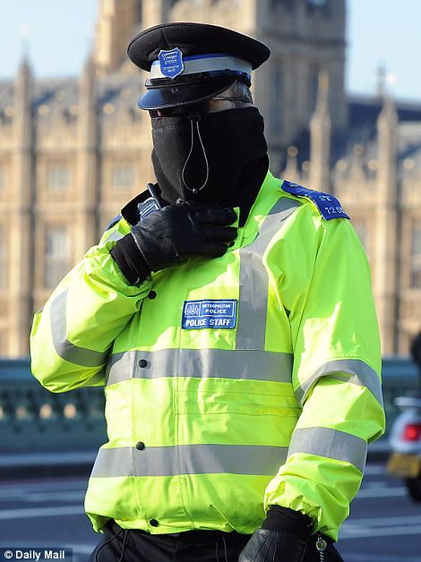 A PCSO pulls his thermal up to keep his nose and ears warm as he crosses Westminster Bridge with the Palace of Westminster in the background