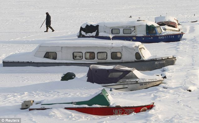 A man passes by snow-covered boats in Kiev