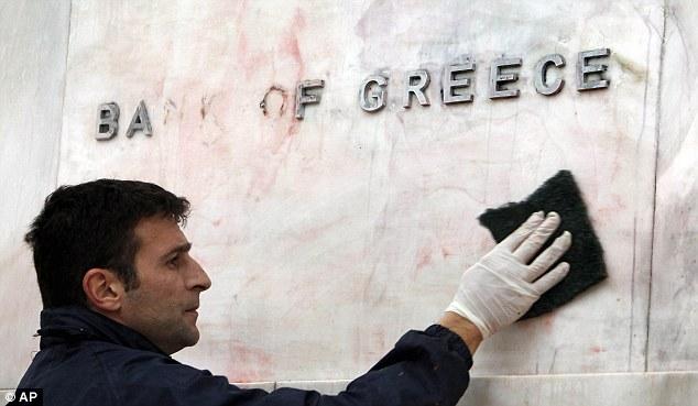 Clear-up: Un trabajador repara el Banco de Grecia muestra que fue salpicado con pintura roja y negro durante los disturbios en Atenas