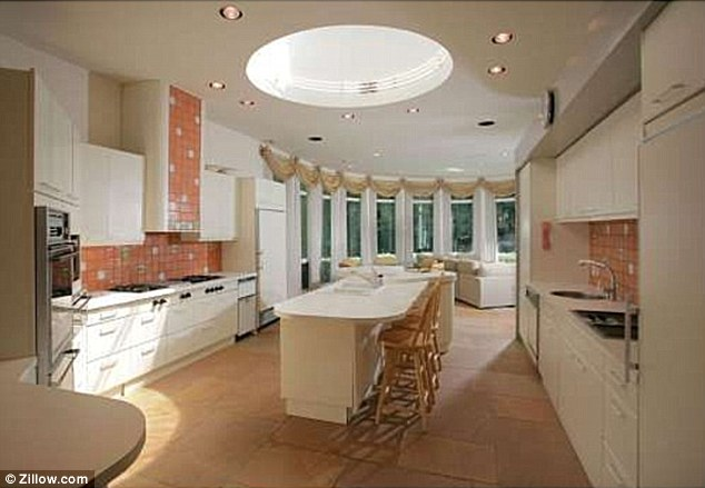 The white stuff: The kitchen features white cabinets and red tiling on the walls with a breakfast bar in the centre