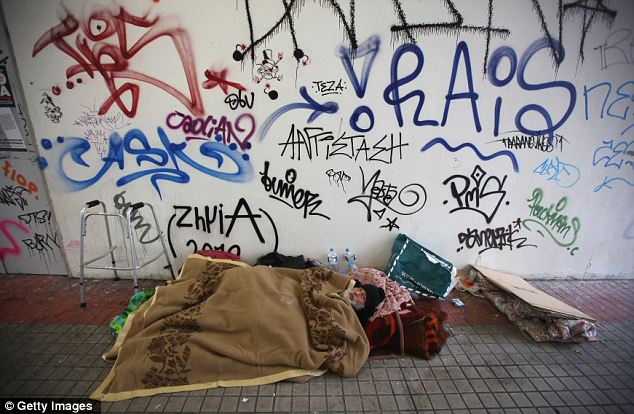A homeless man sleeps rough beneath a graffiti-covered wall in a train station in Athens today