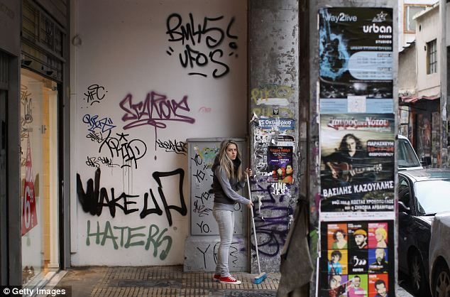 A woman sweeps in front of a graffiti-covered wall in Athens, Greec,e after the riots over cuts demanded in return for a bailout