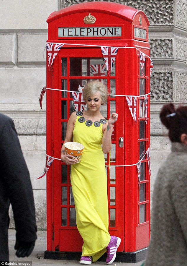 Sunny: In a quick outfit change, Fearne donned a bright yellow maxi dress as she posed next to an iconic red phonebox