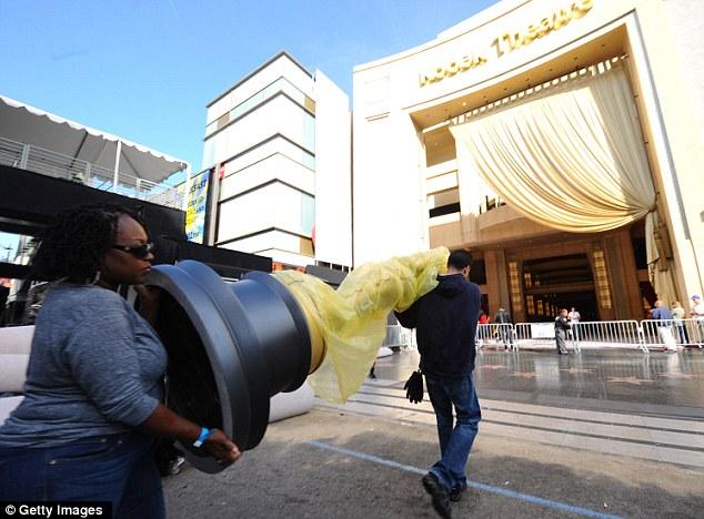 Miembros de la tripulación llevar a una estatua de Oscar de la alfombra roja de los Premios Anuales de la Academia 84 ª en Hollywood y Highland