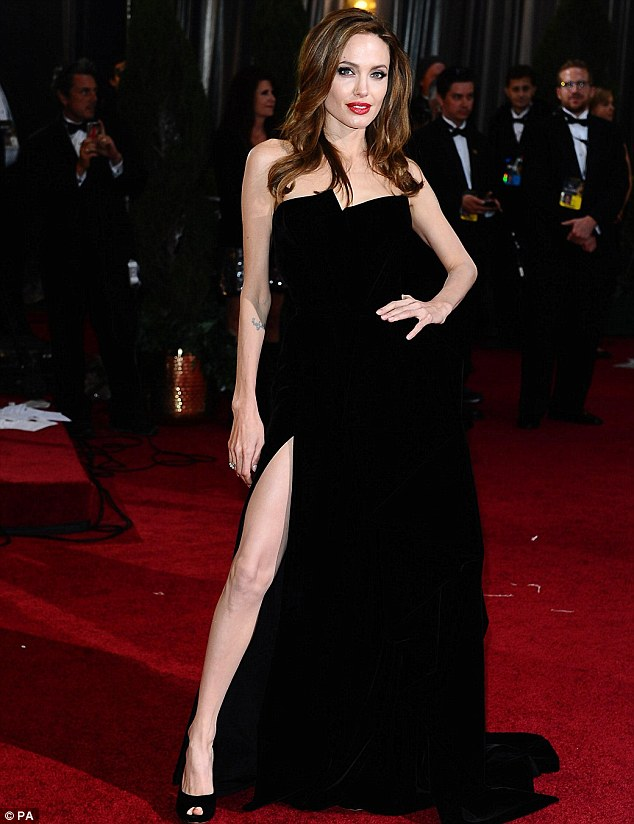 Whole lotta leg: Angelina Jolie flashes more than a peek of her pin as she walks the red carpet at the 84th Academy awards in Hollywood last night
