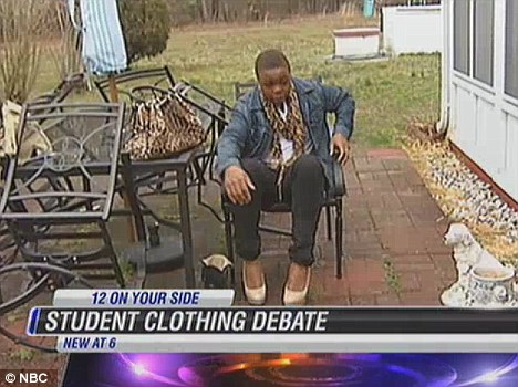 Outfit: The 17-year-old boy wore a denim jacket with a white shirt, leopard skin scarf, black trousers and beige high heels to school earlier this week