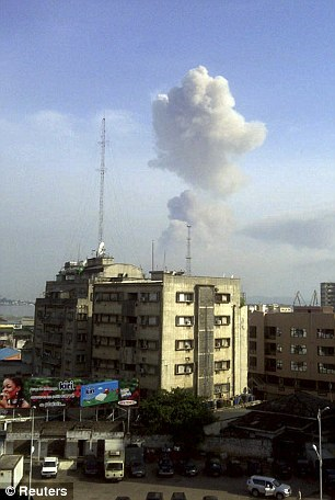 A plume of smoke can be seen rising above the skyline of Brazzaville