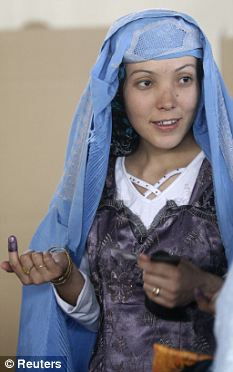 Rights: A woman with an ink-stained finger holds her ID card as she waits to vote in presidential elections at a Kabul polling station in 2009