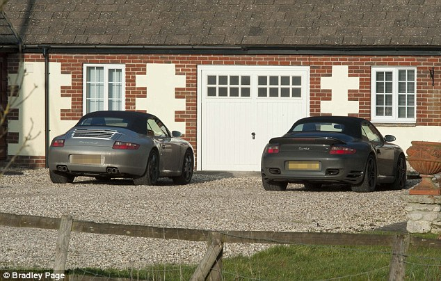 Rich: Two Porsches can be seen parked outside the home of Dr Hibbert near Swindon
