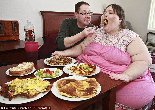 Supersize diet: Susanne Eman, 33 being spoon fed by her boyfriend Parker Clack, 38 at the breakfast table