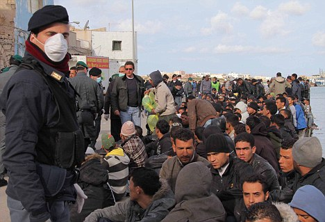 Italian policemen stand guard as migrants wait to leave the Italian island of Lampedusa after thousands fled to the island