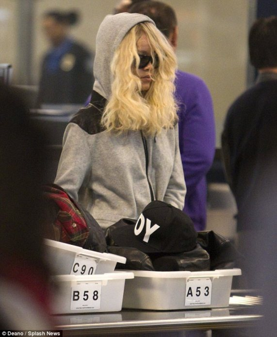 Hat's off: The singer was forced to remove her statement headwear as she made her way through the security at the airport