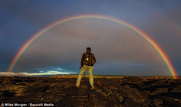 Picture perfect: A fellow photographer is framed by a stunning rainbow as he looks across the horizon