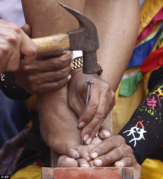 Agony: Woman penitent Percy Valencia has a three inch steel nail hammered into her foot in Paombong, Bulacan province, northern Philippines, today
