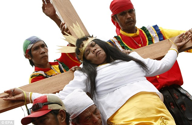 Agony: Percy Valerncia, 41, closes her eyes as she is put on the cross with nails through her hands