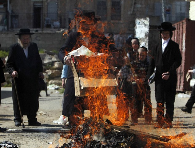 Passover: An ultra-Orthodox Jew holds a box near a fire burning leaven in the Mea Shearim neighbourhood of Jerusalem, ahead of the Jewish holiday of Passover.