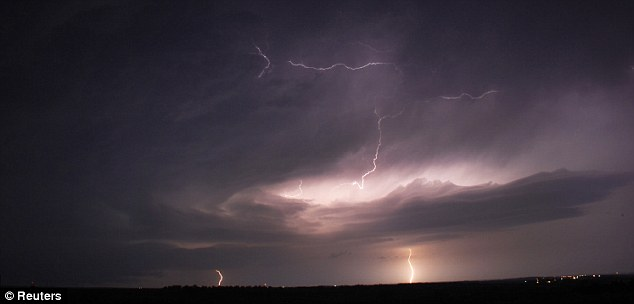 Electrifying: Huge storm clouds shoot out lightning bolts in the skies near the area of Apache Oklahoma - the worst of the storms are predicted for this evening