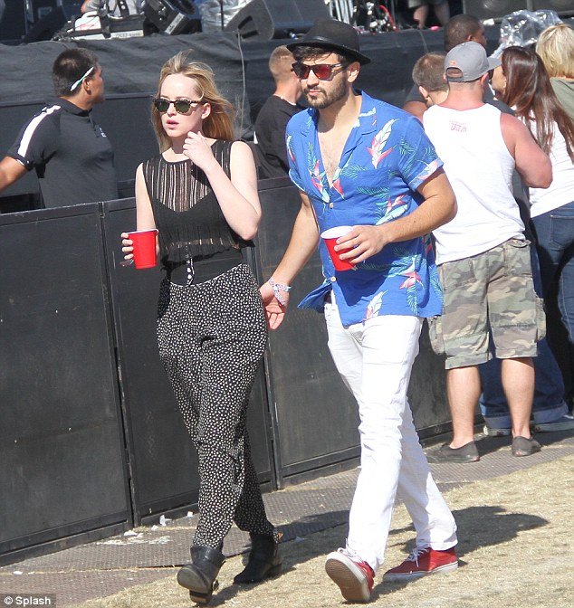 Hipster love: 21 Jump Street actress Dakota Johnson was spotted getting her behind patted by a mystery hipster while checking out AWOL Nation at the Coachella Stage