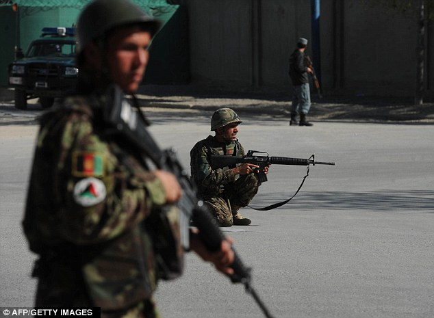 Afghan National Army (ANA) soldiers hold positions near the scene of an attack in Kabul today