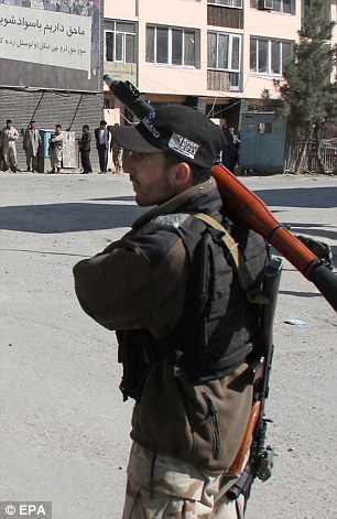 An Afghan security official secures the site after a shooting incident