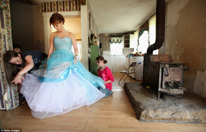 Brittany Brewer, centre, fixes her gown as she prepares for the Owsley County High School prom next to a wood stove in the home where she lives with her grandmother