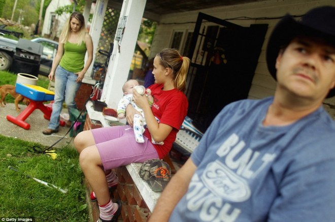Right to left, family members Ronnie Duff, Love Faith Duff, Jacob Lucas and Hope Lucas gather on the porch in Owsley County on April 20 in Booneville